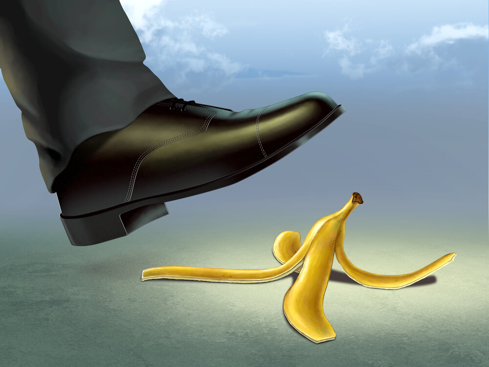 A businessman's foot is just about to step on a banana peel showing the mistakes new manager training could help you avoid