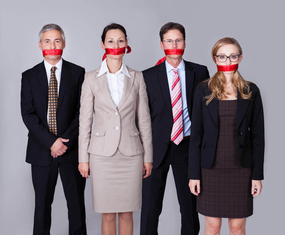 a photo of 4 people with gags over their mouths showing they need new manager training on how to give feedback