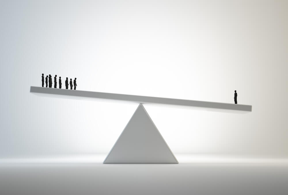 A seesaw shows employees on one end outweighed by one boss posing the question...can a Leader Have Too Much Power