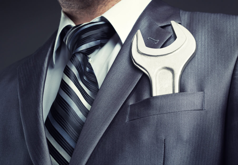 a giant wrench is in a businessman's suit pocket showing how 360-degree feedback supports new manager training